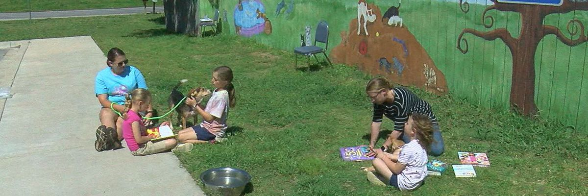 Child volunteers read to dogs at Lawton Animal Welfare