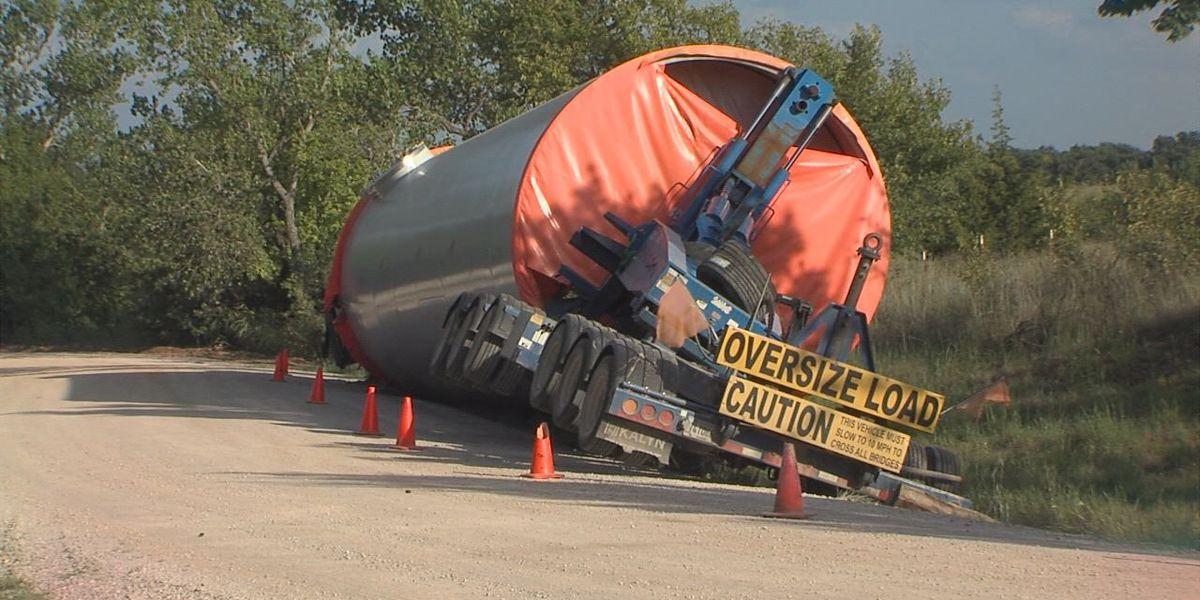 Truck transporting turbine topples